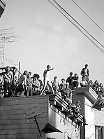 Berkeley students on rooftops watching the riots below. Earlier James Rector, a bystander had been shot observing from another roof, Berkeley California 1969