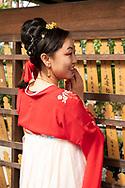 A Japanese woman wearing a kimono and posing for a photograph next to prayer boards at the Fushimi Inari Shrine, Kyoto, Japan
