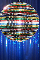 Multi-coloured disco ball in front of blue stage curtain close up