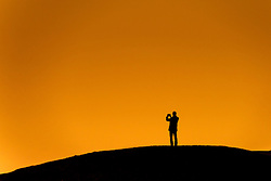 The silhouette of a man taking a photograph during an intense evening sunset.