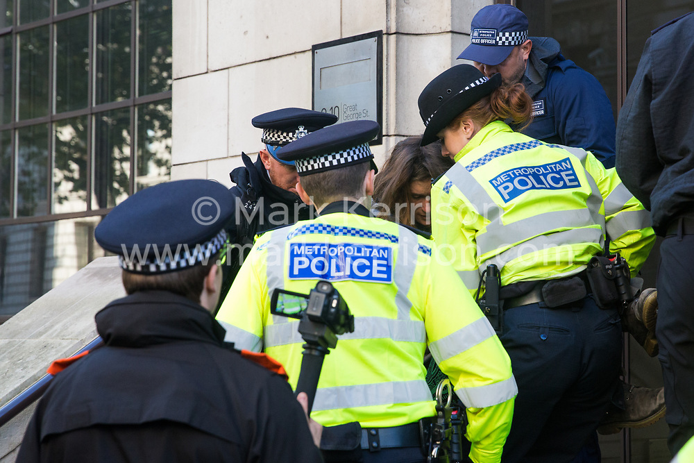 London, UK. 17 October, 2019. Metropolitan Police officers arrest campaigners against the arms trade from Extinction Rebellion Scotland who had glued or locked themselves onto the entrance to the registered office of Lockheed Martin UK in protest against their profiting from arms sold for use in wars and in solidarity with the Kurdish people following the Turkish invasion of Kurdish-held areas of north-east Syria.