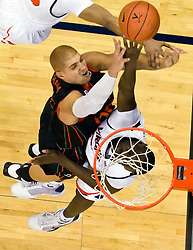 Virginia center Tunji Soroye (21) blocks a shot by Miami (FL) forward Jimmy Graham (00).  The Virginia Cavaliers fell to the Miami Hurricanes 62-55 at the John Paul Jones Arena on the Grounds of the University of Virginia in Charlottesville, VA on February 26, 2009.