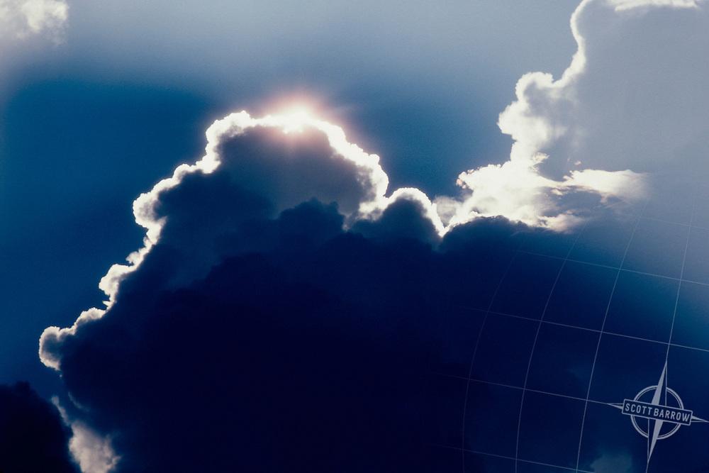 Sun peeking over cumulo nimbus clouds