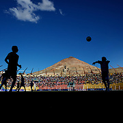'Attitude at Altitude' Football in Potosi, Bolivia'..Action during the match between Real Potosi and Wilstermann at the The Estadio Victor Agustin Ugarte, Potosi, Bolivia, with the infamous Cerro Rico mountain providing the backdrop. Real Potosi won the match 3-0. 2nd May 2010. Photo Tim Clayton...'Attitude at Altitude' Football in Potosi, Bolivia'..The Calvario players greet the final whistle with joyous celebration, high fives and bear hugs the players are sprayed with local Potosina beer after a monumental 3-1 victory over arch rivals Galpes S.C. in the Liga Deportiva San Cristobal. The Cup Final, high in the hills over Potosi. Bolivia, is a scene familiar to many small local football leagues around the world, only this time the game isn't played on grass but a rock hard earth pitch amongst gravel and boulders and white lines that are as straight as a witches nose, The hard surface resembles the earth from Cerro Rico the huge mountain that overlooks the town. .. Sitting at 4,090M (13,420 Feet) above sea level the small mining community of Potosi, Bolivia is one of the highest cities in the world by elevation and sits 'sky high' in the hills of the land locked nation. ..Overlooking the city is the infamous mountain, Cerro Rico (rich mountain), a mountain conceived to be made of silver ore. It was the major supplier of silver for the spanish empire and has been mined since 1546, according to records 45,000 tons of pure silver were mined from Cerro Rico between 1556 and 1783, 9000 tons of which went to the Spanish Monarchy. The mountain produced fabulous wealth and became one of the largest and wealthiest cities in Latin America. The Extraordinary riches of Potosi were featured in Maguel de Cervantes famous novel 'Don Quixote'. One theory holds that the mint mark of Potosi, the letters PTSI superimposed on one another is the origin of the dollar sign...Today mainly zinc, lead, tin and small quantities of silver are extracted from the mine by over 100 co operatives a