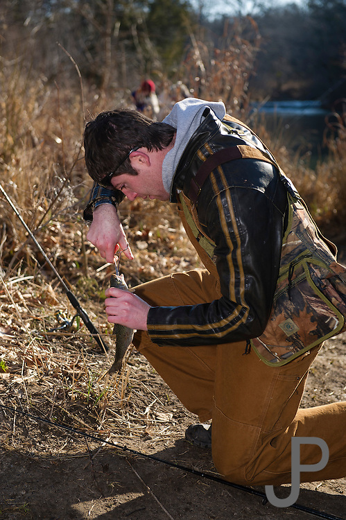Camron Hanks from Oklahoma City removes his hook from a rainbow trout using foreceps to limit damage to the fish.