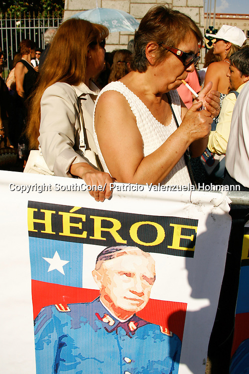 A woman lights a cigarette as she waits in line to salute the dictator whit a banner that reads &quot;Hero&quot;.<br /> December 2006, The Chilean Dictator Augusto Pinochet died in Santiago Chile. As news spread thousands went out the streets either to celebrate o mourn Pinochet who lead the 1973 coup that overthrew the democratically elected president Salvador Allende. Pinochet's 17 year regime killed and disappeared around 4.000 people, tortured and exile around 20.000. On 1989 he lost elections and democracy was regained. He died on late December 2006. December 2006, The Chilean Dictator Augusto Pinochet died in Santiago Chile. As news spread thousands went out the streets either to celebrate o mourn Pinochet who lead the 1973 coup that overthrew the democratically elected president Salvador Allende. Pinochet's 17 year December 2006, The Chilean Dictator Augusto Pinochet died in Santiago Chile. As news spread thousands went out the streets either to celebrate o mourn Pinochet who lead the 1973 coup that overthrew the democratically elected president Salvador Allende. Pinochet's 17 year.