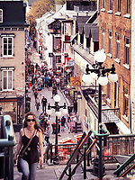 Young woman walking up the stairs of historic street Rue du Petit Champlain on a sunny day.The high angle view of the vibrant shops and restaurants in the background. Quebec, Canada. Ville de Québec. Spring 2017.