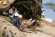 Doris Morrison Amankwaa and her boyfriend Emmanuel Kwaku Yeboah look at pictures they took of each other as they sit on a fishing boat on the beach in Cape Coast, Ghana on Sunday September 7, 2008. The couple was visiting to attend the Oguaa Fetu Afahye Festival, held annually in the coastal town.