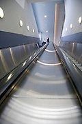 people descending a very long escalator