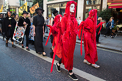 London, UK. 17 September, 2019. Red Brigade climate activists from Extinction Rebellion stage a RIP London Fashion Week Funeral March to call on both the public and the fashion industry to demand an end to London Fashion Week and the unsustainable system of consumption which it promotes. The event included a pause to reflect on the lives already lost and those that will be lost as a result of the climate and ecological crisis. Credit: Mark Kerrison/Alamy Live News