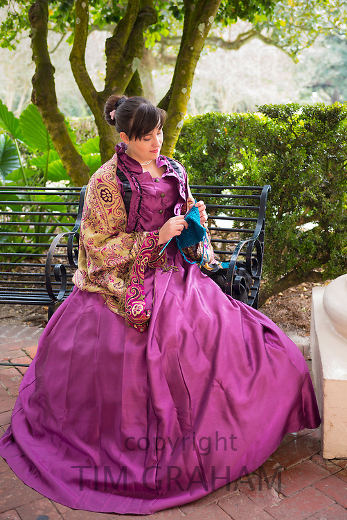 Tour guide in historic costume knitting at Oak Alley plantation antebellum mansion house by Mississippi at Vacherie, USA