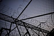 Barbed wire fence at Esperanza men's prison in San Salvador, El Salvador.