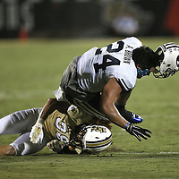 ORLANDO, FL - OCTOBER 09: Jordan Ozerities #38 of the UCF Knights tackles and knocks loose the helmet of Algernon Brown #24 of the Brigham Young Cougars at Bright House Networks Stadium on October 9, 2014 in Orlando, Florida. (Photo by Alex Menendez/Getty Images) *** Local Caption ***Jordan Ozerities; Algernon Brown