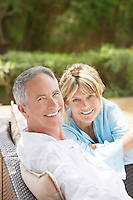 Contented middle-aged couple sitting outdoors on chairs portrait