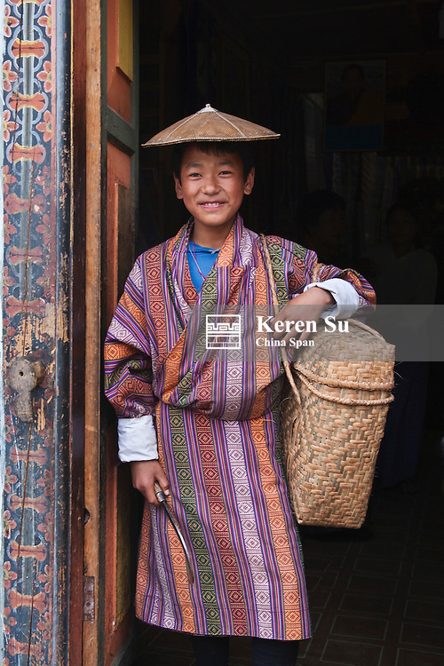 Portrait of a farmer boy wearing bamboo hat, Bumthang, Bhutan