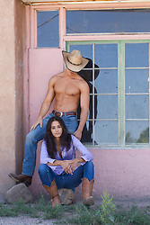 sexy shirtless cowboy near a beautiful girl seated by a home in New Mexico