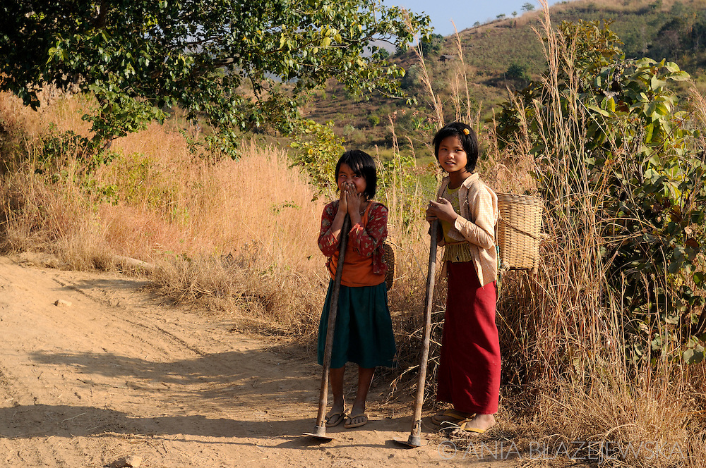 Myanmar/Burma. Girls resting on the road after finishing their work.
