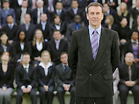 Business man standing in front of business people sitting on tribune portrait