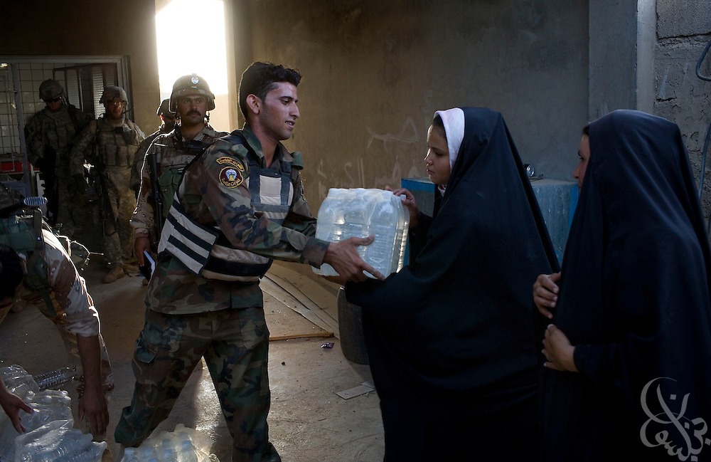 Iraqi soldiers hand out emergency food and water supplies to residents in a humanitarian mission organized by U.S. Army 1-23 Strykers in the Mufrek neighborhood of Bacouba, Iraq June 22, 2007. As U.S. and Iraqi soldiers continue to sweep western Bacouba in search of Al Qaeda fighters and safe houses, many residents remain isolated by a vehicle curfew and local stores have begun to run short on basic supplies creating fears of a looming humanitarian crisis.