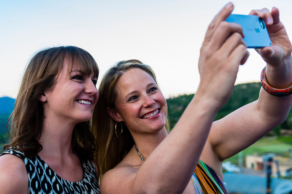 """Two young women take a """"selfie"""" (self-portrait) with their camera at the Westin Snowmass Resort, Snowmass Village (Aspen), Colorado USA."""