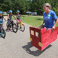 Tracy Peters crosses the street with her truck causing the bikers to come to a stop before proceeding iin the CATCH Kids bike rodeo at the Haven Acres  Boys & Girls Club on Thursday.
