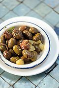 CHEFCHAOUEN, MOROCCO - 27th APRIL 2016 -  Plate of Moroccan green olives on a tiled table background, Chefchaouen - the blue city - Rif Mountains, Northern Morocco.
