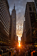 Manhattanhenge on July 11, 2016 from 34th Street and Park Avenue. The term was coined by famed astrophysicist Neil deGrasse Tyson and has grown exponentially in popularity. Thousands of people turn out on major east / west streets in Manhattan to see the sun align with the canyons of skyscrapers.