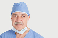 Close-up portrait of senior male surgeon over gray background