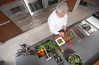 Mid- adult chef prepares salad  overview