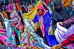 Uyghur women shop clothes at market in Khotan, Xinjiang province in China.