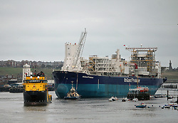 """Licensed to London News Pictures. 18/10/2013. North Tyneside, UK, In another milestone for the improving fortunes of the River Tyne's offshore industrial base, Enquest Producer, a 248m, 92,000tonne Floating Production Storage Offshore (FPSO) unit is the largest vessel to arrive on the Tyne for 10 years. She has been towed from Hamburg to Wallsend-based OGN for commissioning before being placed in Enquest's Alma/Galia development which is revitalising the Argyll oilfield. The work on the Tyne is expected to take 8 months and has created a number of jobs. <br /> <br /> The vessel arrived under tow and without engines making it a challenging job for the Port of Tyne's team of <br /> Pilots.<br /> <br /> Captain Mike Nicholson, Port of Tyne Harbour Master, said: """"We have developed a good level of experience in <br /> handling FPSO's but working with a 'dead ship' with no power always requires careful planning.<br /> """"Conditions have to be just right, the weather will be critical, we will need winds of force 4 or less with <br /> benign sea and swell. Three of our most senior Pilots will be employed to coordinate five tugs with a total <br /> pulling force of over 400 tonnes.""""<br /> <br /> Seven oil production wells and two water injection wells will be feeding crude to the EnQuest Producer, <br /> capable of processing 57,000 barrels per day and storing 625,000 barrels (almost 100 million litres) of <br /> crude oil. EnQuest Producer has been undergoing major modification and life extension work at theHamburg <br /> shipyard of Blohm and Voss before being moved to the Tyne for completion. <br /> <br /> Enquest Producer will be Located in the central North Sea, 310km south-east of Aberdeen, in water depth of <br /> approximately 80m.<br /> <br /> Argyll was first discovered in 1971 and four years later was the first North Sea field to produce oil, <br /> before being decommissioned twice over the subsequent decades.      <br /> <br /> Photo credit: Adrian Don/LNP"""