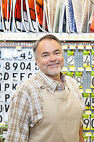 Portrait of a happy mature salesperson in hardware store