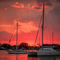 The sun peeks over the horizon at daybreak along the West Palm Beach, Fla., waterfront setting the sky ablaze.