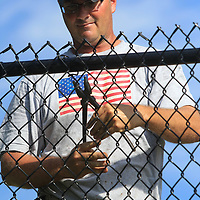 Chris Hughes, an employee with Ivy Fence in Tupelo, ties down fencing to its post during installation of a new fence around the Basketball courts at Gumtree Park in Tupelo Monday morning.