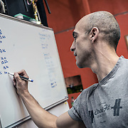 British instructor Edward Hines marks the whiteboard with final training times for each student.