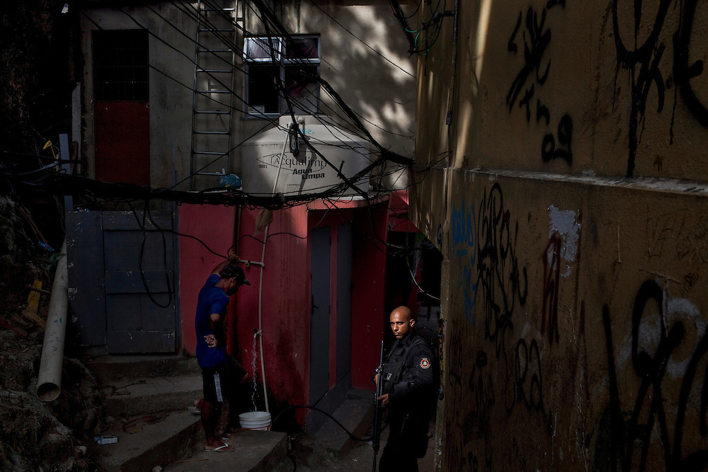 A resident collects some water as a special forces officer patrols nearby during an incursion by security forces into 'Rocinha', one of Brazil's biggest slums controlled by drug traffickers, on November 13, 2011, in Rio de Janeiro, Brazil. Photo by Mauricio Lima for The New York Times