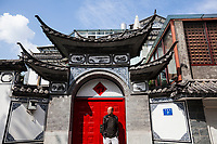 A portrait of artist Ye Yongqing in front of the red doors to his home in Dali City, China.