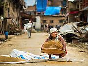04 AUGUST 2015 - KHOKANA, NEPAL: A woman shucks rice in a street clogged with earthquake debris in Khokana, a village about an hour from Kathmandu. Three months after the earthquake, roads in many rural villages are still blocked by earthquake debris. The Nepal Earthquake on April 25, 2015, (also known as the Gorkha earthquake) killed more than 9,000 people and injured more than 23,000. It had a magnitude of 7.8. The epicenter was east of the district of Lamjung, and its hypocenter was at a depth of approximately 15km (9.3mi). It was the worst natural disaster to strike Nepal since the 1934 Nepal–Bihar earthquake. The earthquake triggered an avalanche on Mount Everest, killing at least 19. The earthquake also set off an avalanche in the Langtang valley, where 250 people were reported missing. Hundreds of thousands of people were made homeless with entire villages flattened across many districts of the country. Centuries-old buildings were destroyed at UNESCO World Heritage sites in the Kathmandu Valley, including some at the Kathmandu Durbar Square, the Patan Durbar Squar, the Bhaktapur Durbar Square, the Changu Narayan Temple and the Swayambhunath Stupa. Geophysicists and other experts had warned for decades that Nepal was vulnerable to a deadly earthquake, particularly because of its geology, urbanization, and architecture.     PHOTO BY JACK KURTZ