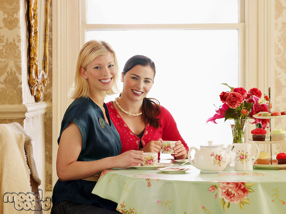 Two young women sitting at dining table drinking tea portrait