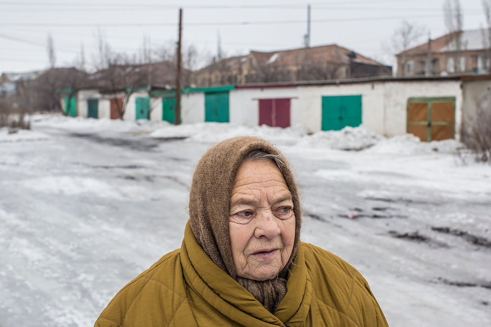 KOMUNAR, UKRAINE - JANUARY 27, 2015: Galina Alekseyeva, 80, takes a walk in the cold in Komunar, Ukraine. Like many local residents, she spent more than a month living in a basement when the village was the site of heavy fighting between pro-Russia rebels and Ukrainian forces over the summer. CREDIT: Brendan Hoffman for The New York Times