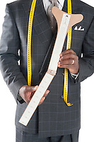 Midsection of tailor holding a measuring device