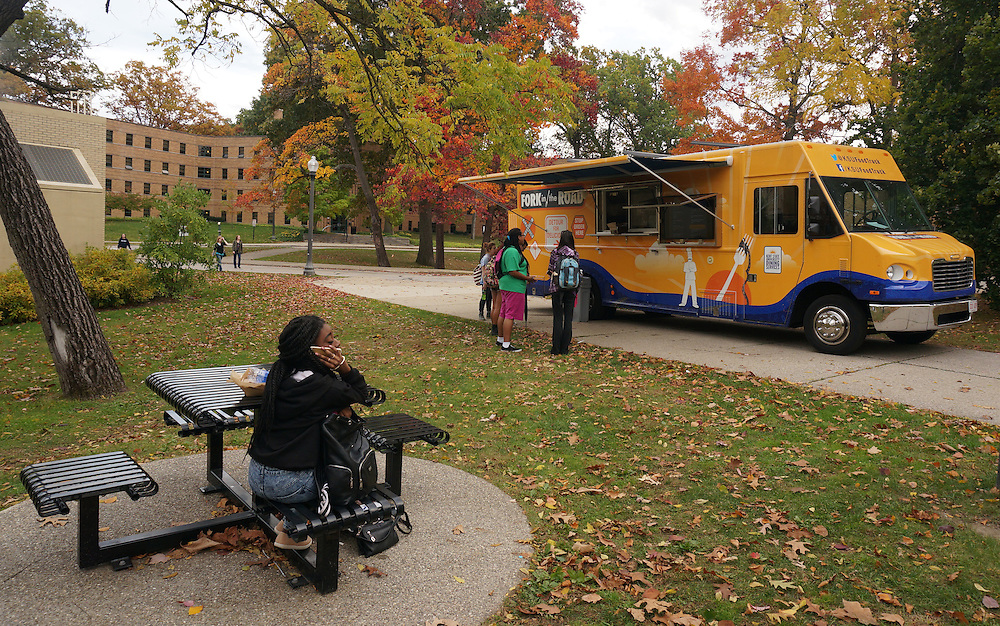 Students wait in line at the Fork in the Road food truck parked near White Hall on a fall afternoon. The truck parks at a different location each day.
