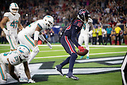 Houston Texans wide receiver DeAndre Hopkins (10) is covered by Miami Dolphins cornerback Xavien Howard (25) and Miami Dolphins strong safety T.J. McDonald (22) as he catches a fourth quarter touchdown pass for a 42-23  Texans lead during the NFL week 8 regular season football game against the Miami Dolphins on Thursday, Oct. 25, 2018 in Houston. The Texans won the game 42-23. (©Paul Anthony Spinelli)