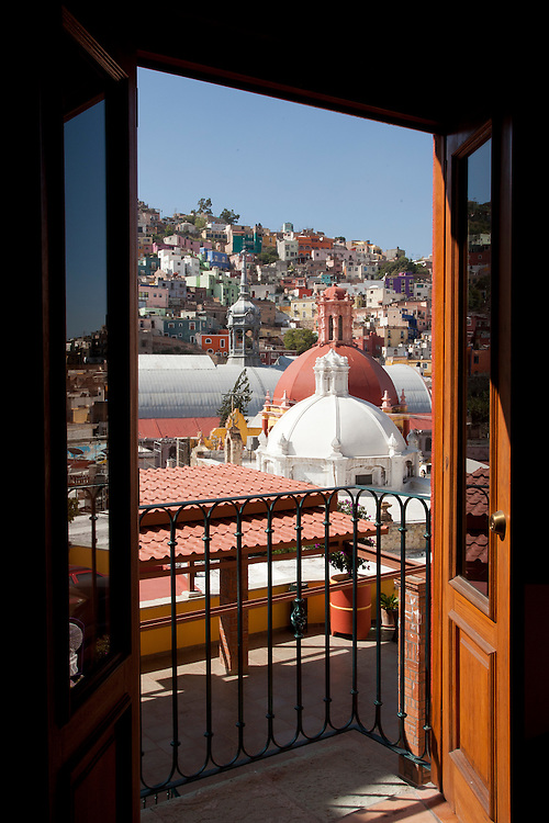 North America, Mexico, Guanajuato State, Guanajuato, church cupolas and colorful houses on hillside, viewed through hotel room doors.  Guanajuato is UNESCO World Heritage Site.  PR