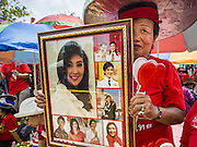 April 6, 2014 - Bangkok, Bangkok, Thailand - <br /> <br /> Red Shirts Rally in Bangkok Suburbs<br /> <br /> A Red Shirt supporter holds up pictures of Yingluck Shinawatra, the embattled Thai Prime Minister during a rally in the Bangkok suburbs Sunday. Red Shirts and supporters of the government of Yingluck Shinawatra, the Prime Minister of Thailand, gathered in a suburb of Bangkok this weekend to show support for the government. The Thai government is dealing with ongoing protests led by anti-government activists. Legal challenges filed by critics of the government could bring the government down as soon as the end of April. The Red Shirt rally this weekend was to show support for the government, which public opinion polls show still has the support of most of the electorate.<br /> ©Exclusivepix