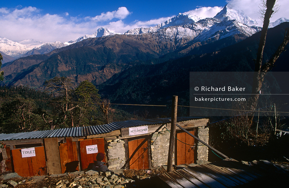 Outdoor showers with a magnificent Himalayan view on the Annapurna Sanctuary trekking route in central Nepal. A tourist waits for a cubical to become free beneath the spectacular backdrop of snow-peaked mountains. Communities here partly-depend on the agriculture of rice-growing but also on the passing tourist trade. Western trekkers from all over the world walk through these tiny communities on their way up the series of climbing trails of the Annapurna Conservation Sanctuary circuit, a sometimes rigorous walk from the low hills of Pokhara to the higher altitudes of Annapurna, the (26,000 feet (8,000 metre) peak. To be greeted by so much choice is the most rewarding experience and the offer of hot showers is about the best reward for so much exertion.