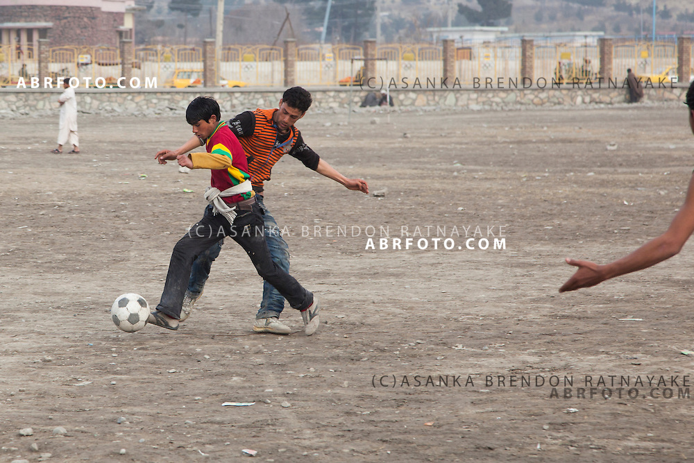 Men playing soccer on the olympic fields outside of Ghazi Stadium in Kabul