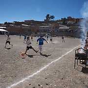 'Attitude at Altitude' Football in Potosi, Bolivia'..Local players take part in the finals series at the Liga Deportiva San Cristobal cup finals series  on the stone and gravel surface high in the hills over Potosi, as a barbercue is prepared pitch side. Potosi, Bolivia 9th May 2010....'Attitude at Altitude' Football in Potosi, Bolivia'..The Calvario players greet the final whistle with joyous celebration, high fives and bear hugs the players are sprayed with local Potosina beer after a monumental 3-1 victory over arch rivals Galpes S.C. in the Liga Deportiva San Cristobal. The Cup Final, high in the hills over Potosi. Bolivia, is a scene familiar to many small local football leagues around the world, only this time the game isn't played on grass but a rock hard earth pitch amongst gravel and boulders and white lines that are as straight as a witches nose, The hard surface resembles the earth from Cerro Rico the huge mountain that overlooks the town. .. Sitting at 4,090M (13,420 Feet) above sea level the small mining community of Potosi, Bolivia is one of the highest cities in the world by elevation and sits 'sky high' in the hills of the land locked nation. ..Overlooking the city is the infamous mountain, Cerro Rico (rich mountain), a mountain conceived to be made of silver ore. It was the major supplier of silver for the spanish empire and has been mined since 1546, according to records 45,000 tons of pure silver were mined from Cerro Rico between 1556 and 1783, 9000 tons of which went to the Spanish Monarchy. The mountain produced fabulous wealth and became one of the largest and wealthiest cities in Latin America. The Extraordinary riches of Potosi were featured in Maguel de Cervantes famous novel 'Don Quixote'. One theory holds that the mint mark of Potosi, the letters PTSI superimposed on one another is the origin of the dollar sign...Today mainly zinc, lead, tin and small quantities of silver are extracted from the mine by over 100 co operatives and private m