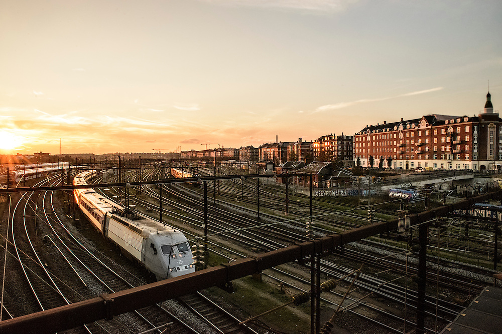 A train rumbles in to Copenhagen Central Station as it passes under Dybbølsbro at sunset.