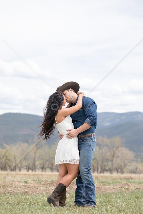romantic cowboy couple outdoors on a mountain range